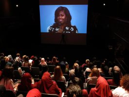 Michelle Obama on screen speaking to audience of girls (© AP Images)
