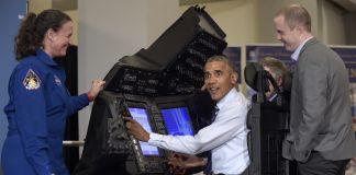 El presidente Obama sentado frente a monitores junto a una mujer con uniforme de la NASA y un hombre con traje (© AP Images)
