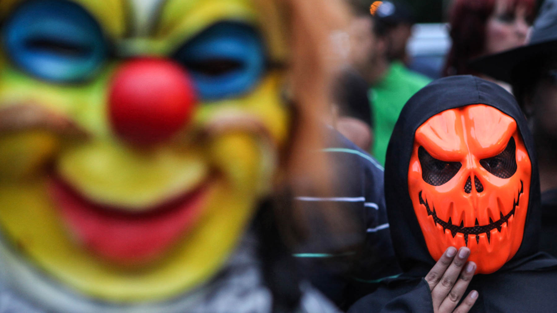 People wearing brightly colored masks (© AP Images)