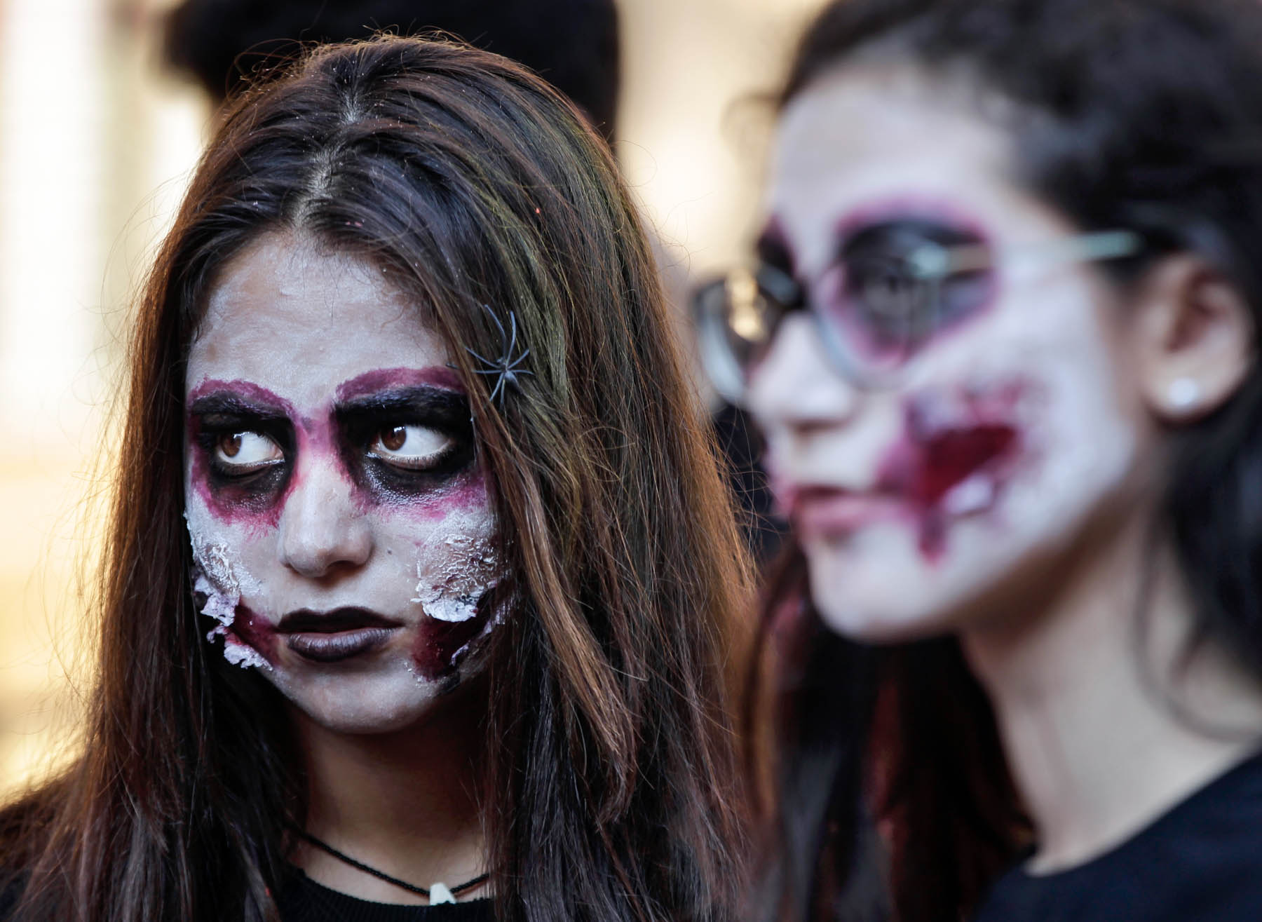 Two women wearing zombie face paint (© AP Images)