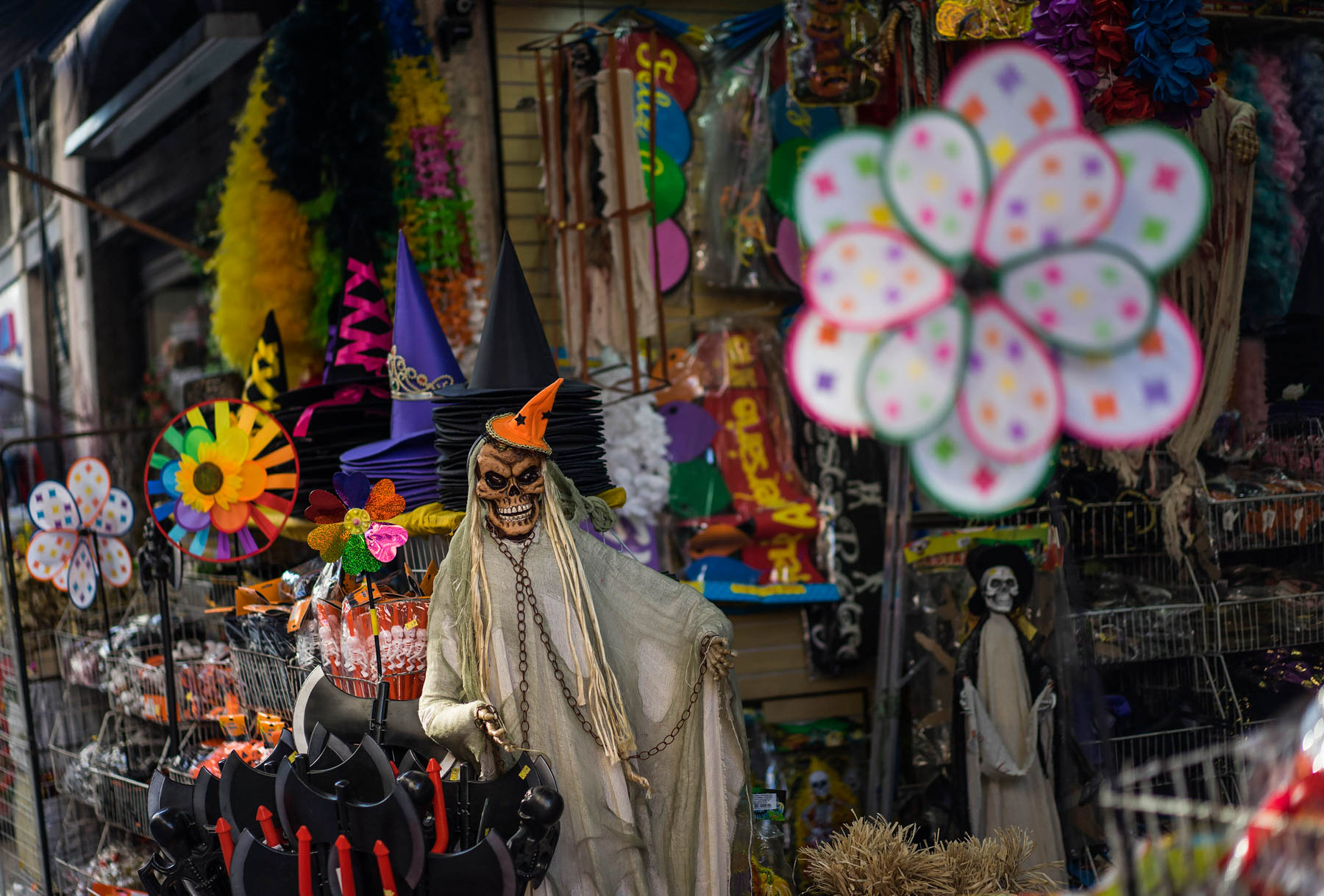 Smiling skeleton in Halloween costume standing among colorful items for sale (© AP Images)