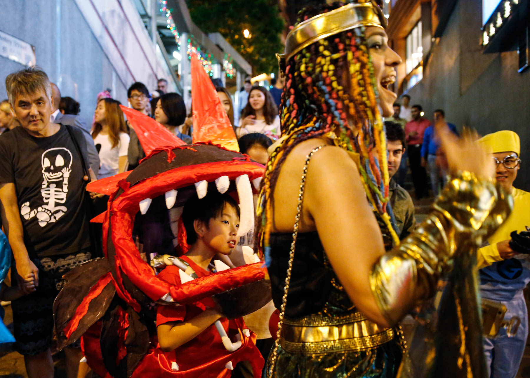 Crowd surrounding child dressed in dragon costume (© AP Images)