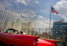 People in red car looking at U.S. and Cuban flags (© AP Images)