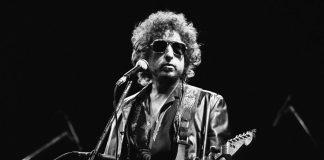 دھوپ کے چشمے پہنے ہوئے اور گٹار پکڑے ہوئے، باب ڈِلن مائیکروفون کے سامنے کھڑے ہیں۔ (© AP Images)