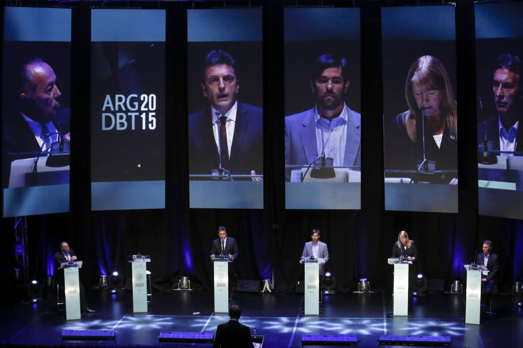 Five people at lecterns on stage, their images on large screens behind them (© AP Images)