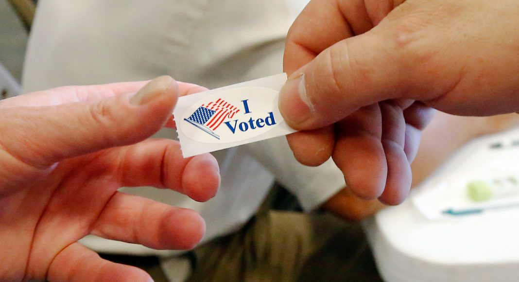 Hands holding 'I voted' sticker (© AP Images)