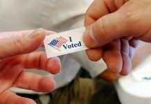 Hands holding 'I voted' sticker (© AP Images)