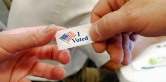"""ہاتھوں میں 'میں نے ووٹ ڈالا ہے"""" کا سٹکر۔ (© AP Images)"""