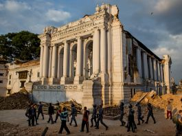 A white, columned building with people walking by (© AP Images)