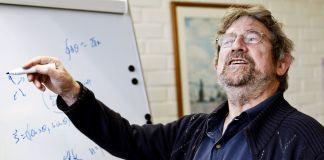 El ganador de un Nobel Michael Kosterlitz en frente de una pizarra blanca (© AP Images)