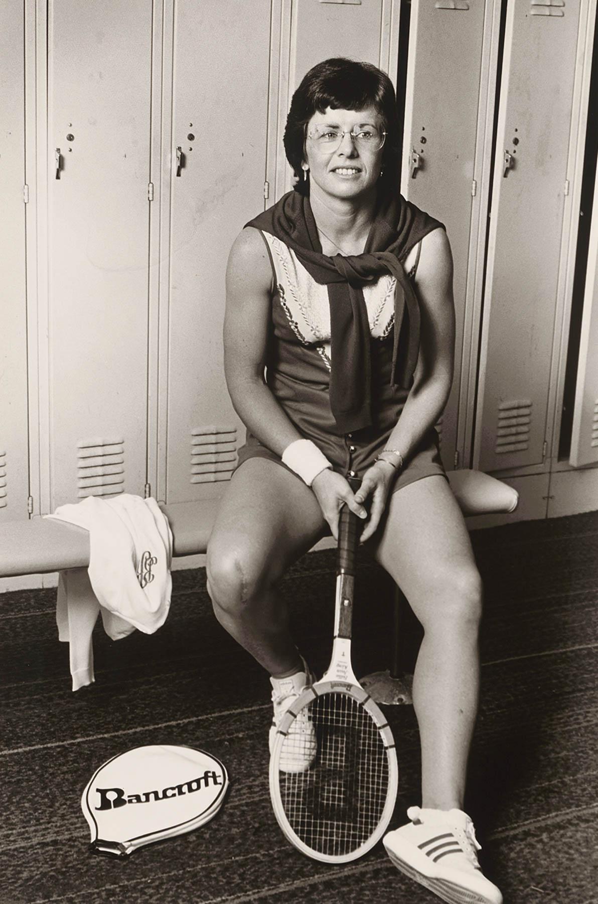 La estrella de tenis Billie Jean King sentada en un vestuario, sosteniendo una raqueta de tenis (© Lynn Gilbert)