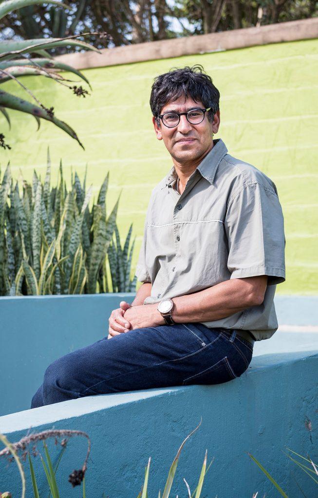 Deenan Pillay sentado ao ar livre em um jardim (Ben Gilbert/Wellcome Trust)