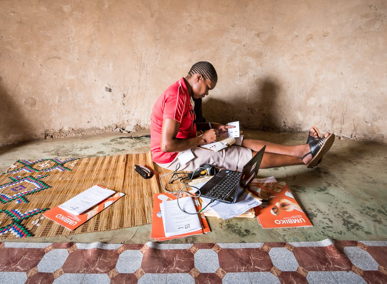 Mulher sentada em esteira de palha com laptop e cadernos ao seu redor (Ben Gilbert/Wellcome Trust)