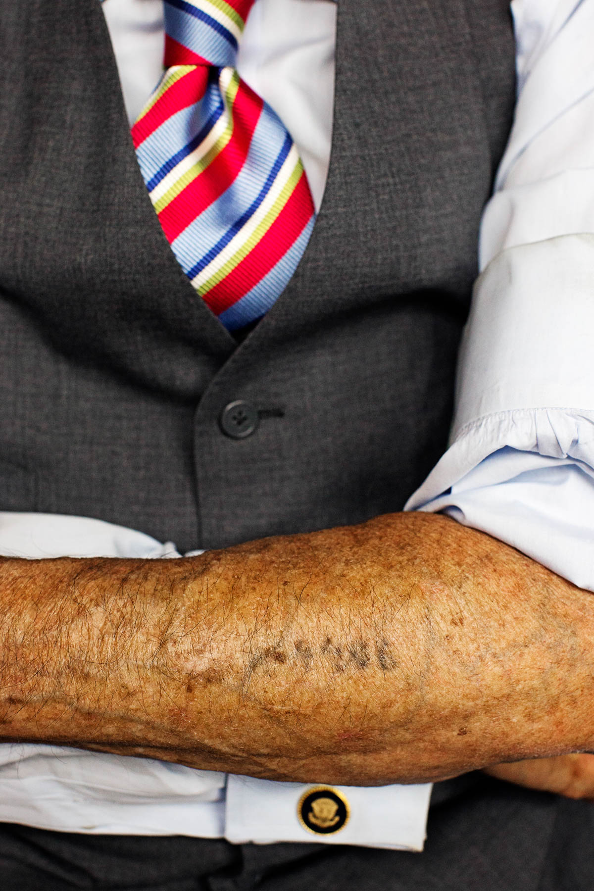 Man crossing his tattooed arm over his suit vest and tie (© Getty Images/Joseph Victor Stefanchik)