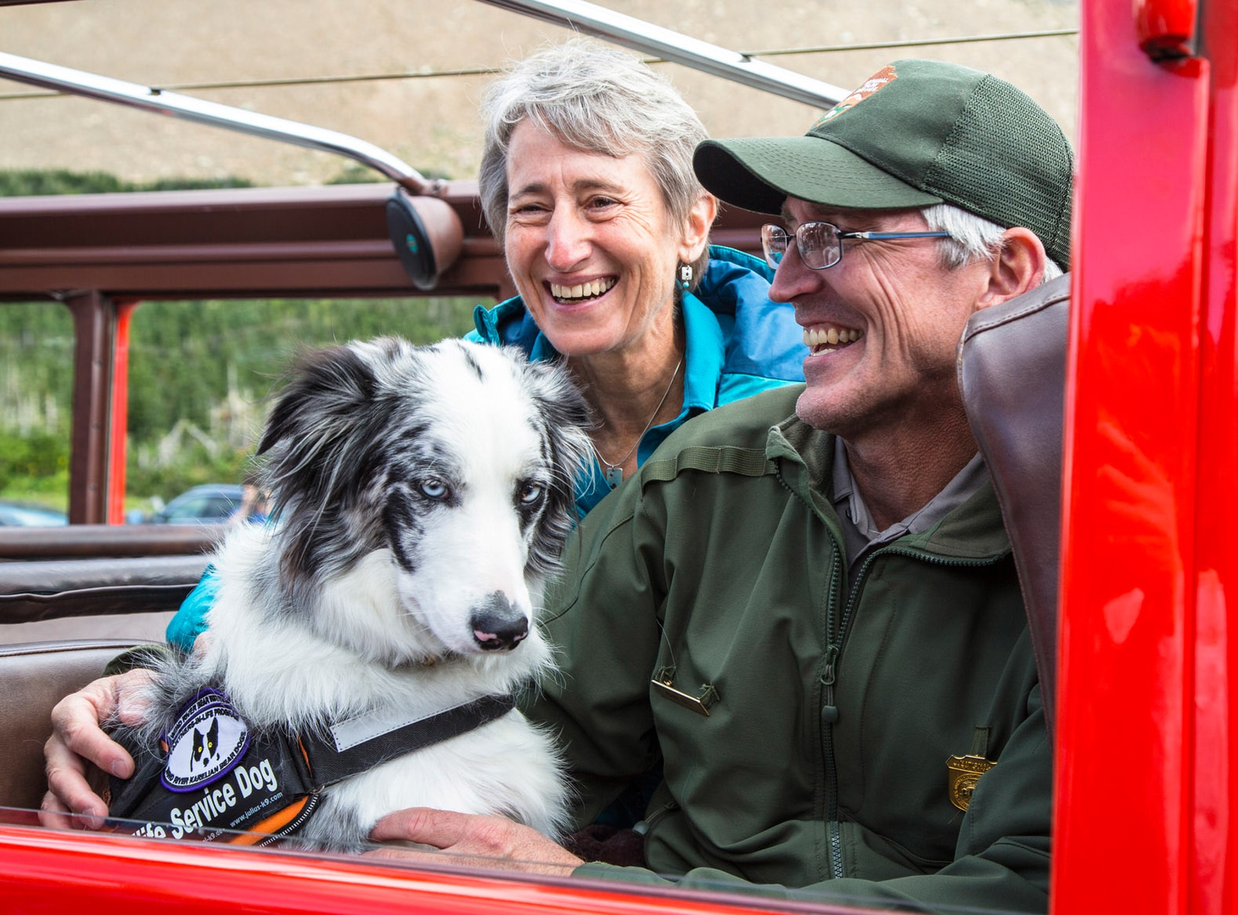 Two people holding dog while riding in car (NPS/Jacob W. Frank)