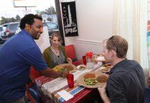 Man serving dishes of food to customers in restaurant (Nameer Al-Rubaye)