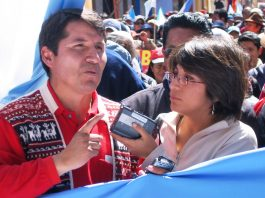 Mabel Cáceres interviewing man while surrounded by people (International Women's Media Foundation)