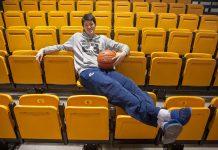 Yuta Watanabe souriant, assis dans des gradins, un ballon de basket à la main (Département d'État/D.A. Peterson)