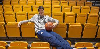 Homem segurando uma bola de basquete e sentado em arquibancada com cadeiras amarelas (Depto. de Estado/D.A. Peterson)