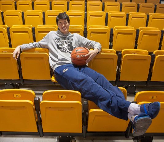 Man sitting on yellow bleacher seats holding basketball (State Dept./D.A. Peterson)