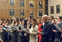 Crowd of people standing in a large room with portraits on the walls (State Dept./Mary E. Nagel)