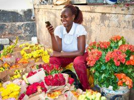 سيدة سوداء محاطة بالزهور تنظر إلى هاتفها وهي تبتسم . (© AP Images)