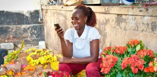 A black woman surrounded by flowers looking at a phone (© AP Images)