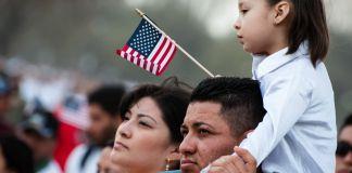 Child sitting on man's shoulders holding American flag (Shutterstock)