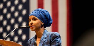 Ilhan Omar s'exprime devant un micro, avec un drapeau américain en arrière-plan. (© Lorie Shaull/Flickr)