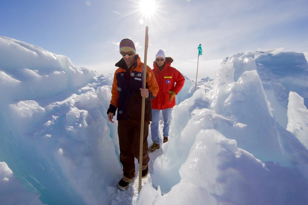 Guide with stick and John Kerry walking on path through ice (State Dept.)