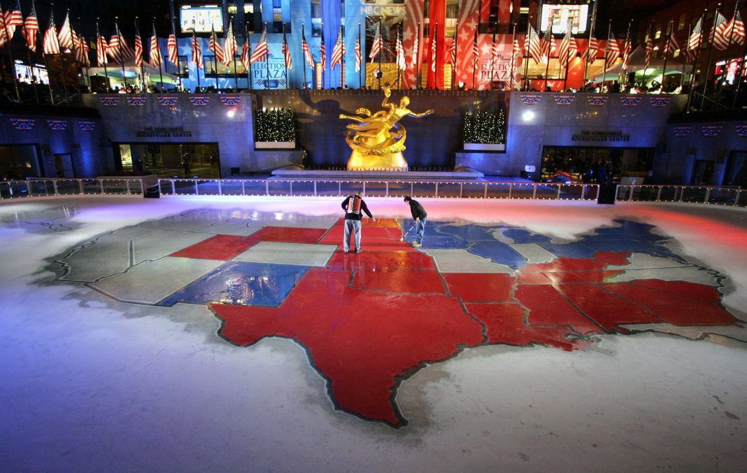 Two people changing colors on large floor map of U.S. (© AP Images)