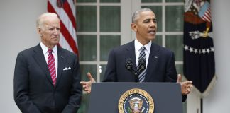 Vice President Biden standing next to President Obama at lectern (© AP Images)
