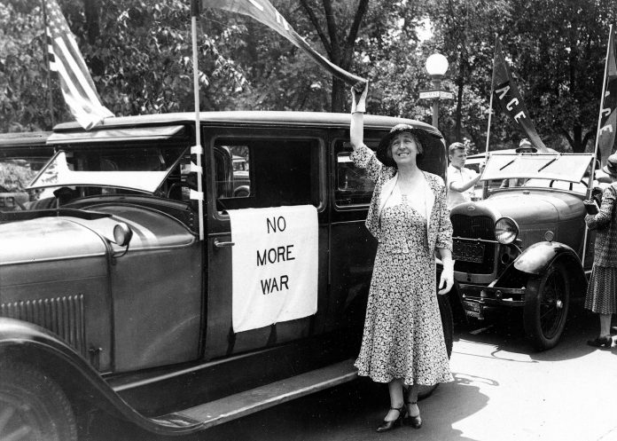 "Jeannette Rankin standing next to car with ""No more war"" sign (© AP Images)"