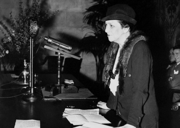 Frances Perkins standing at desk with microphones (© AP Images)