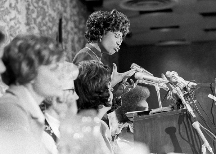 Shirley Chisholm speaking at lectern, with others seated next to her (© AP Images)