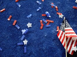 Flag and confetti on blue carpet (© AP Images)
