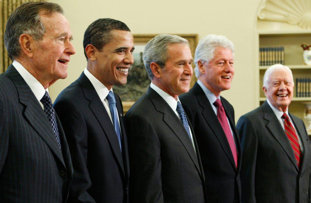 جارج ایچ ڈبلیو بش، بارک اوباما، جارج ڈبلیو بش، بل کلنٹن اور جمی کارٹر اکٹھے کھڑے ہیں۔ (© AP Images)