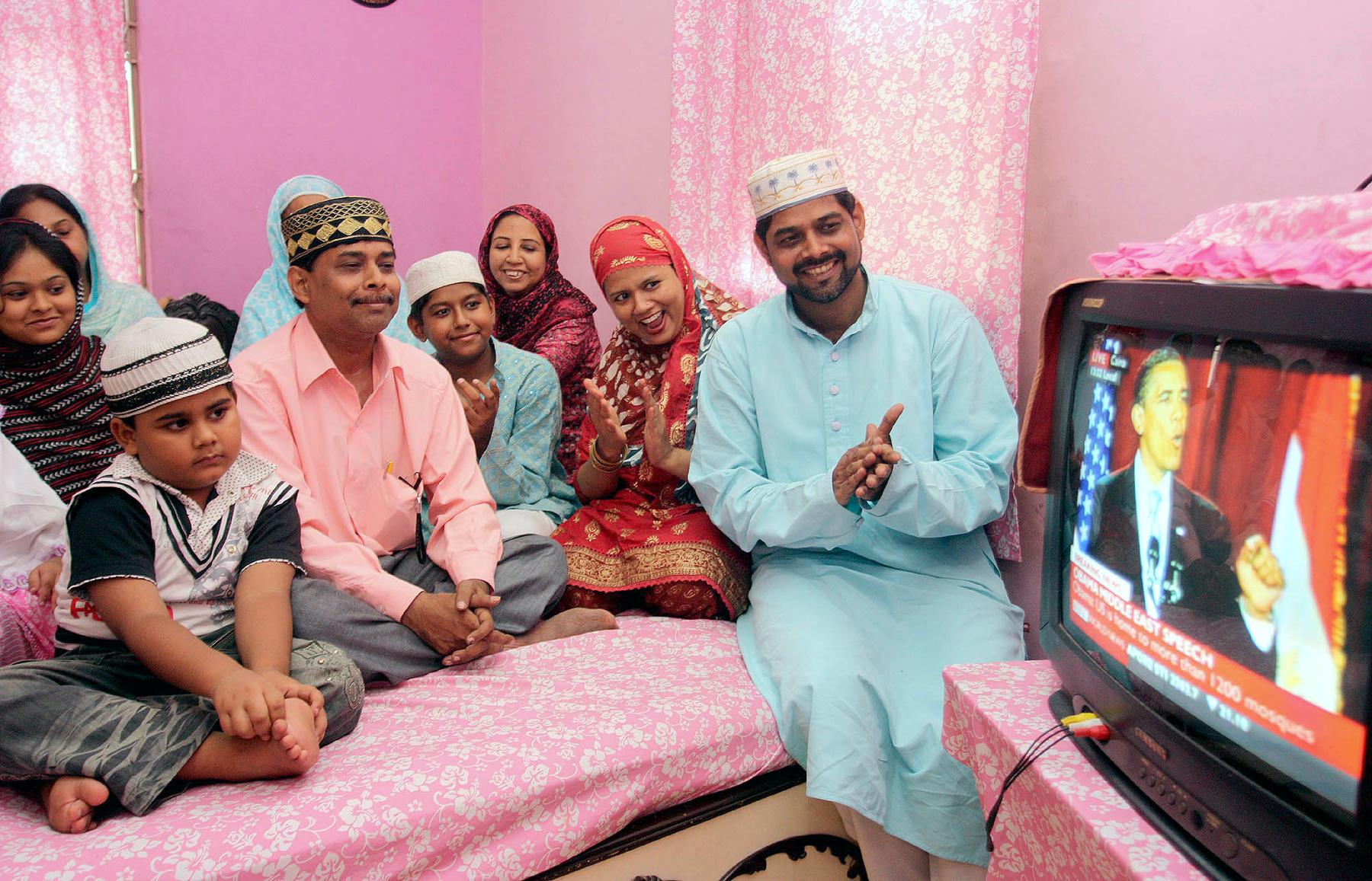 People sitting in room watching TV (© AP Images)