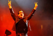 Bono raising hands in peace signs (© AP Images)