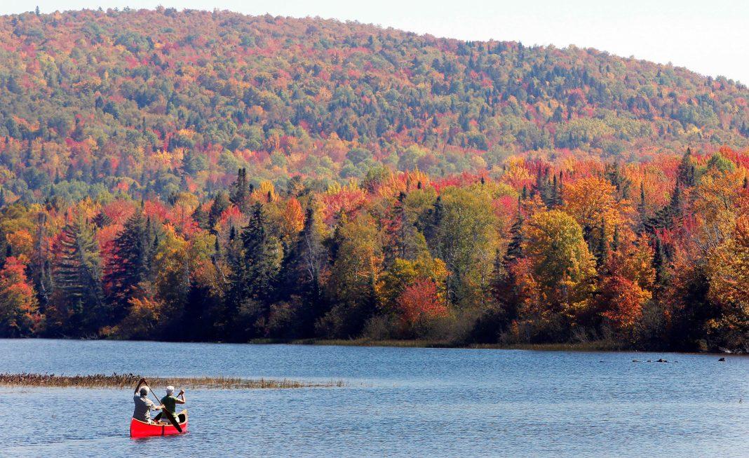 Dos personas en una canoa con un lago al fondo, bosque con follaje otoñal al fondo (© AP Images)
