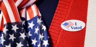 Person wearing 'I voted' sticker and American flag scarf (© AP Images)
