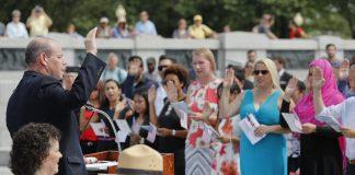 حلف برداری کی تقریب میں لوگوں نے ہاتھ بلند کیے ہوئے ہیں۔ (© AP Images)