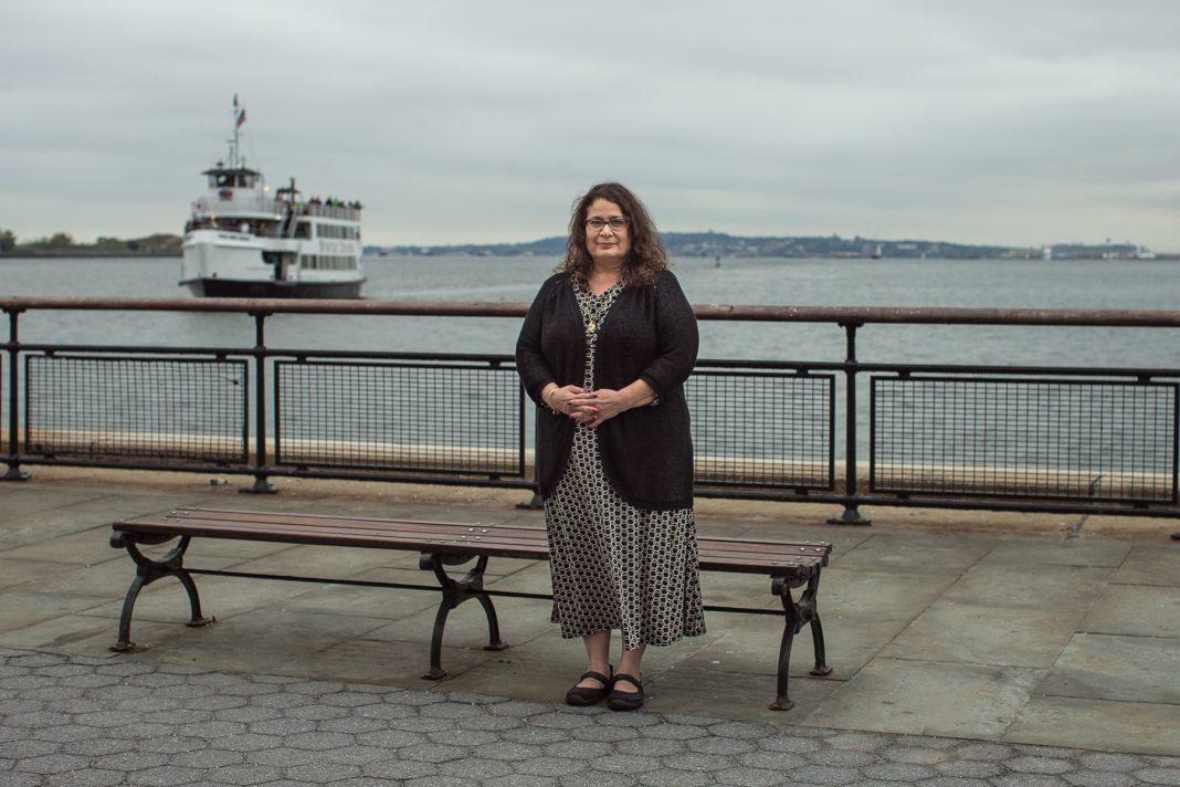 Une femme posant pour la photo sur un quai, un ferry en arrière-plan (© AP Images)