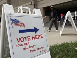 """""""Vote Here"""" sign outside building (© AP Images)"""