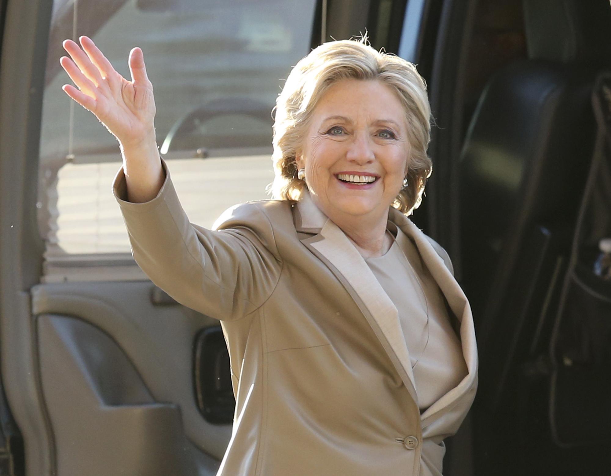 Hillary Rodham Clinton waving and smiling at camera (© AP Images)