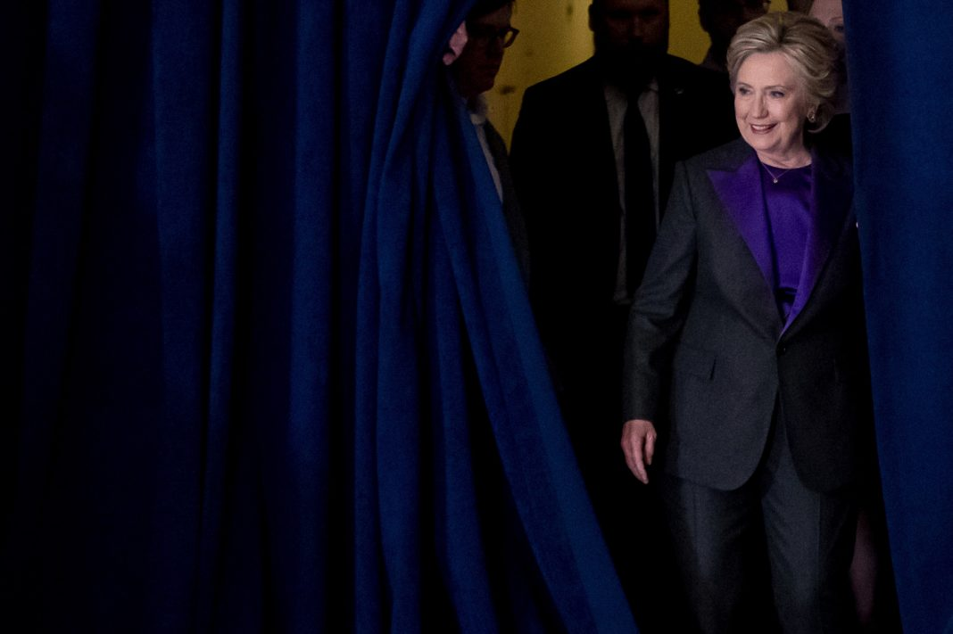 Hillary Clinton walking onstage from behind curtain (© AP Images)