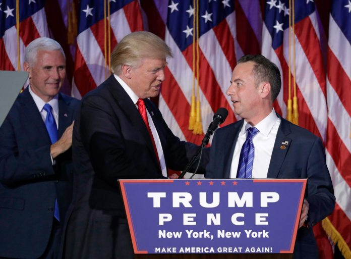 Donald Trump shaking hands with Reince Priebus behind a podium (© AP Images)