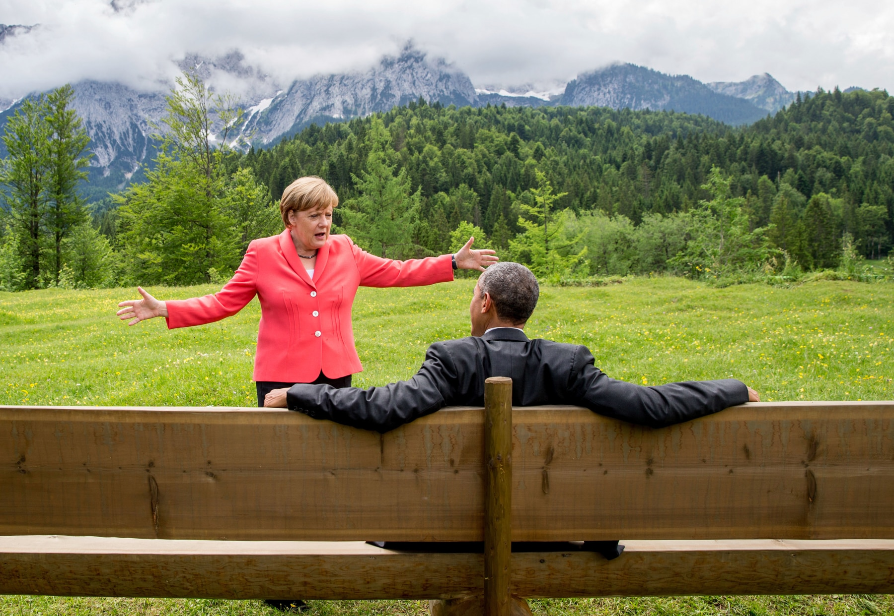Angela Merkel standing and gesturing as President Obama sits on bench, with mountains and lush greenery in background (© AP Images)