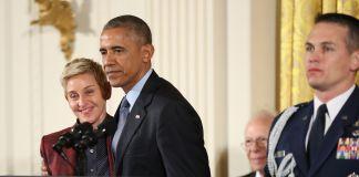 Ellen DeGeneres de pie al lado del presidente Obama ante un podio y otro hombre sosteniendo una medalla (© AP Images)