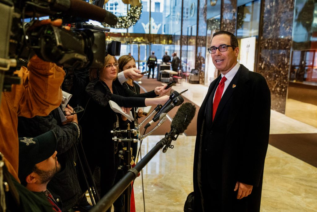 Steven Mnuchin talking to people holding microphones and recorders (© AP Images)